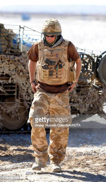 Prince Harry carries a 9mm pistol and wears body armour in the desert on February 18 2008 in Helmand Province Afghanistan