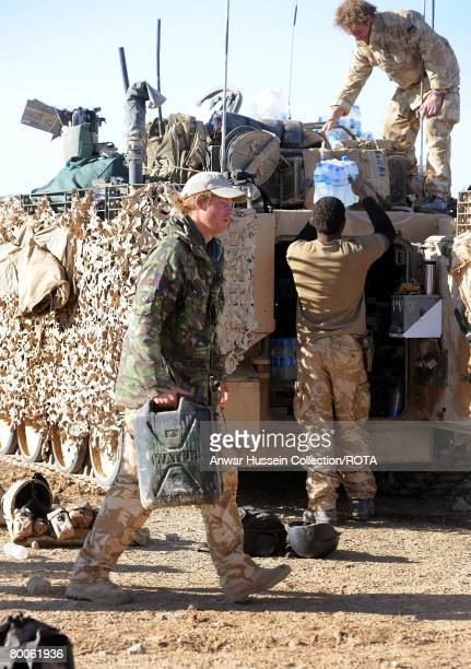 Prince Harry carries a water can to his Spartan armoured vehicle in the desert on February 18 2008 in Helmand Province Afghanistan