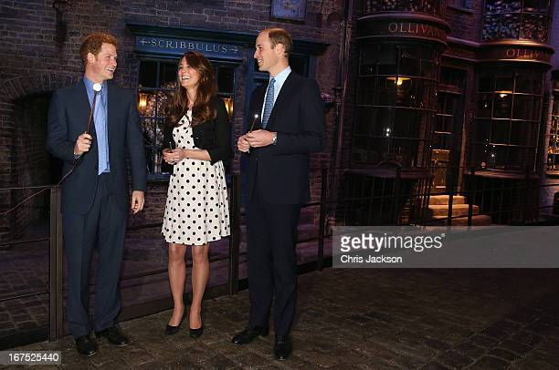 Prince Harry, Catherine, Duchess of Cambridge and Prince William, Duke of Cambridge share a joke Ollivanders Wand Shop on the set used to depict...