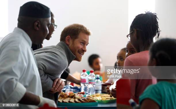 Prince Harry chats to children as he visits a Fit and Fed February school holiday activity programme at the Roundwood Youth Centre on February 15...