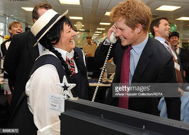 Prince Harry closes a deal with broker Amanda Hartnell at the offices of city traders ICAP on December 10, 2008 in London, England. The Prince...