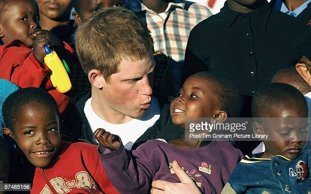 Prince Harry cuddles children Mutsu and Lintle in the grounds of the Mants'ase children's home, while on a return visit to Lesotho in southern Africa...