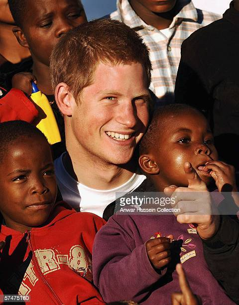 Prince Harry cuddles children Mutsu and Lintle , in the grounds of the Mants'ase childrens home while on a return visit to Lesotho on April 24, 2006...