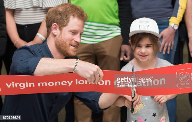 Prince Harry cuts a ribbon with a young girl as he officially opens the Virgin Money London Marathon Expo at ExCel on April 19 2017 in London England