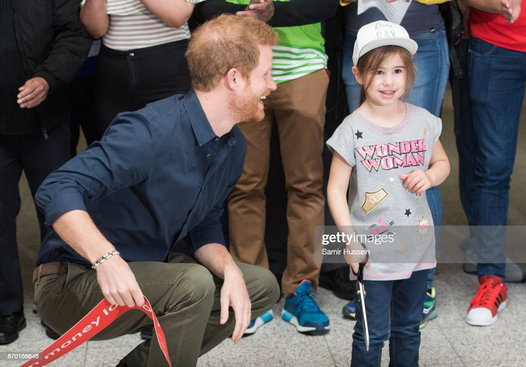 Prince Harry cuts a ribbon with a young girl as he officially opens the Virgin Money London Marathon Expo at ExCel on April 19, 2017 in London, England.
