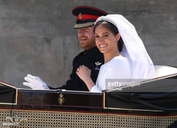 Prince Harry Duke of Sussex and Duchess of Sussex in the Ascot Landau carriage leave Windsor Castle during the procession after getting married St...