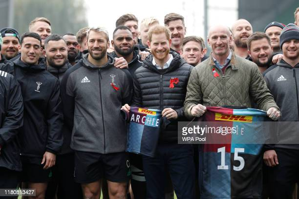 Prince Harry, Duke of Sussex and former rugby player Gareth Thomas pose with gift shirts next to Harlequin rugby club members and their captain Chris...