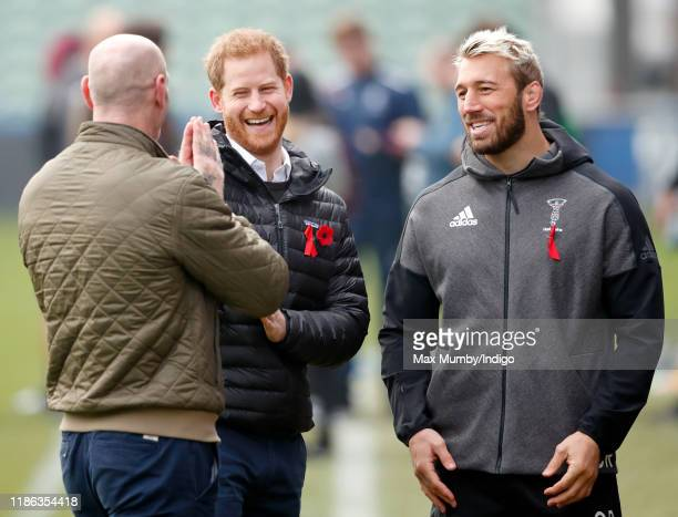 Prince Harry, Duke of Sussex and Gareth Thomas talk with Harlequins team captain Chris Robshaw as they attend a Terrence Higgins Trust event ahead of...