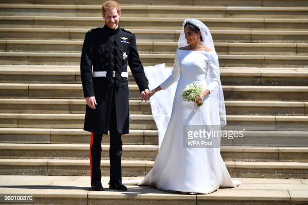Prince Harry Duke of Sussex and his wife Meghan Duchess of Sussex leave from the West Door of St George's Chapel Windsor Castle in Windsor on May 19...