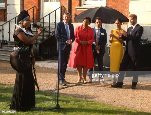 Prince Harry Duke of Sussex and Meghan Duchess of Sussex accompanied by Commonwealth secretary general Baroness Scotland listen to music group...