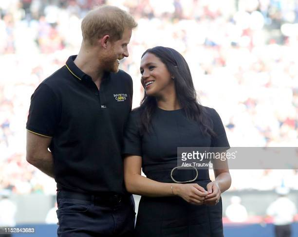 Prince Harry Duke of Sussex and Meghan Duchess of Sussex accompany Invictus Games competitors on the field for the ceremonial first pitch before game...