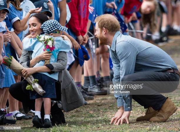 Prince Harry Duke of Sussex and Meghan Duchess of Sussex are greeted by fiveyearold Luke Vincent as they arrive at Dubbo Airport on October 17 2018...