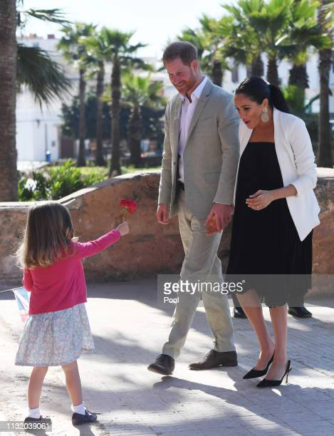 Prince Harry Duke of Sussex and Meghan Duchess of Sussex are greeted by a young wellwisher as they walk through the walled public Andalusian Gardens...