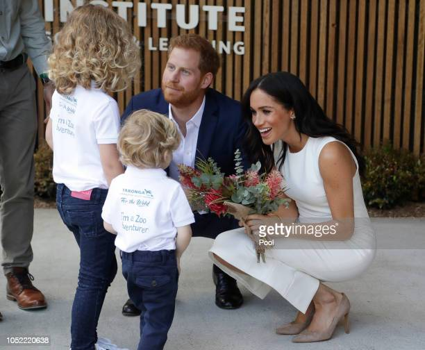 Prince Harry Duke of Sussex and Meghan Duchess of Sussex are presented with native flowers from children Dasha Gallagher and Finley Blue during a...