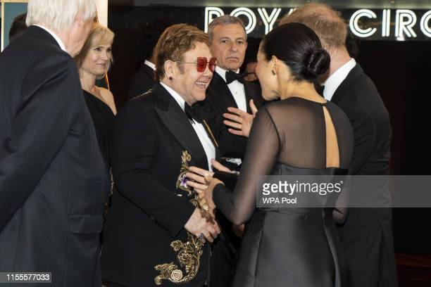 "Prince Harry, Duke of Sussex and Meghan, Duchess of Sussex chat with British singer-songwriter Elton John at the European Premiere of Disney's ""The..."