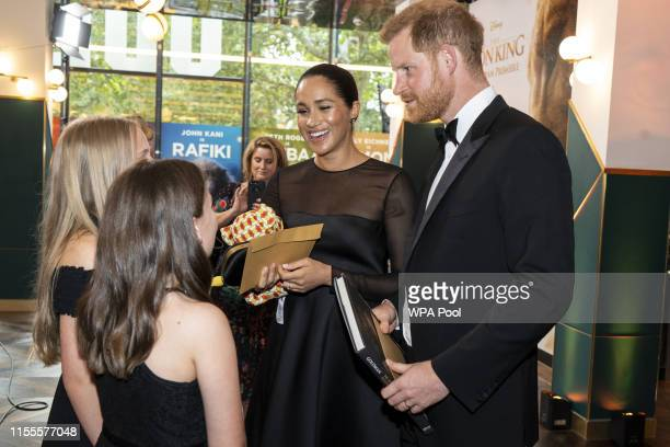 """Prince Harry, Duke of Sussex and Meghan, Duchess of Sussex chat with young children of Disney executives at the European Premiere of Disney's """"The..."""