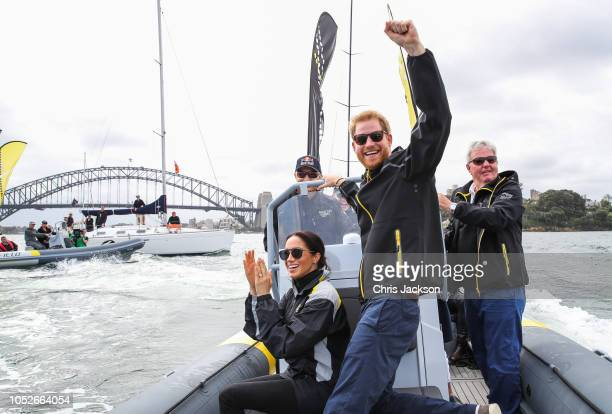 Prince Harry Duke of Sussex and Meghan Duchess of Sussex cheering on sailers on Sydney harbour during day two of the Invictus Games Sydney 2018 at...