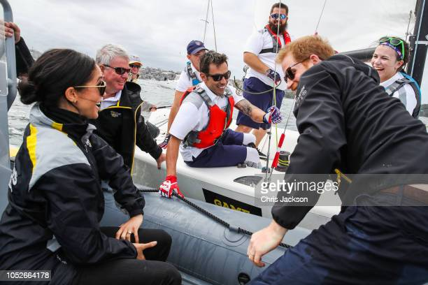 Prince Harry, Duke of Sussex and Meghan, Duchess of Sussex cheering on and talking to sailers on Sydney harbour during day two of the Invictus Games...