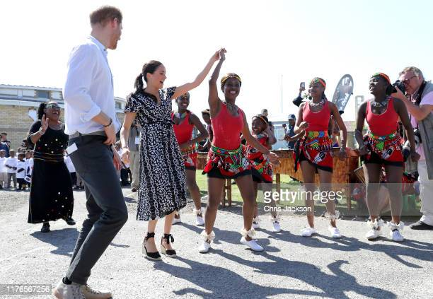 Prince Harry Duke of Sussex and Meghan Duchess of Sussex dance as they visit a Justice Desk initiative in Nyanga township during their royal tour of...