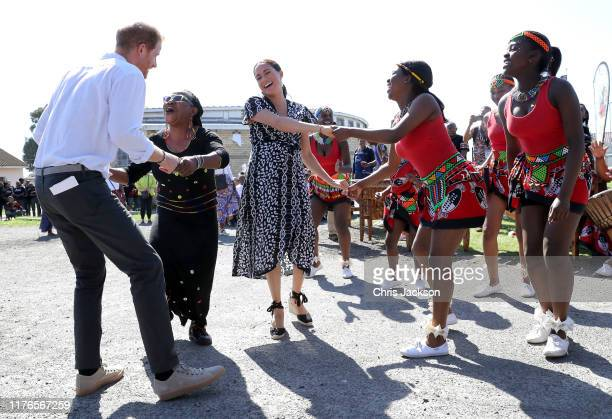 Prince Harry, Duke of Sussex and Meghan, Duchess of Sussex dance as they visit a Justice Desk initiative in Nyanga township, during their royal tour...