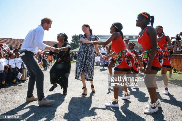 TOPSHOT Prince Harry Duke of Sussex and Meghan Duchess of Sussex dance as they arrive for a visit to the Justice desk an NGO in the township of...