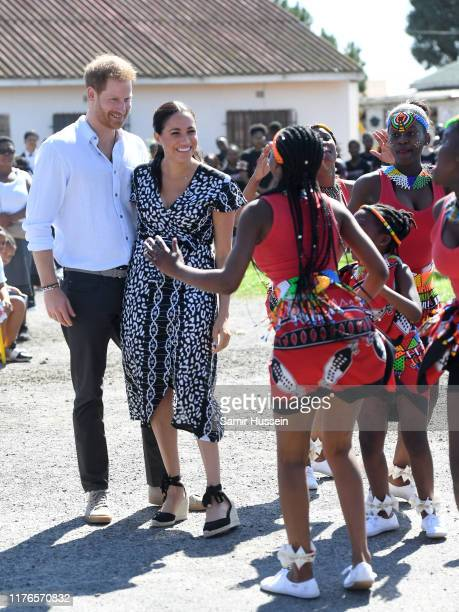Prince Harry, Duke of Sussex and Meghan, Duchess of Sussex dance with local as they visit a Justice Desk initiative in Nyanga township, during their...