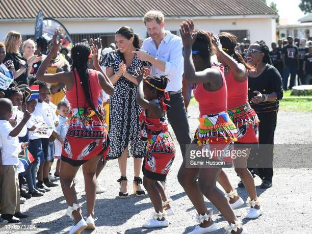 Prince Harry, Duke of Sussex and Meghan, Duchess of Sussex dance with locals as they visit a Justice Desk initiative in Nyanga township, during their...