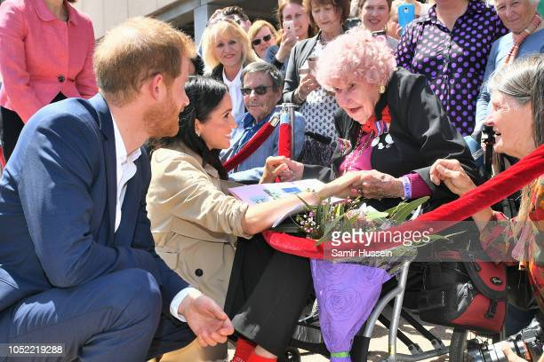Prince Harry Duke of Sussex and Meghan Duchess of Sussex greet royal fan and war widow Daphne Dunne as they arrive for a public walkabout at the...