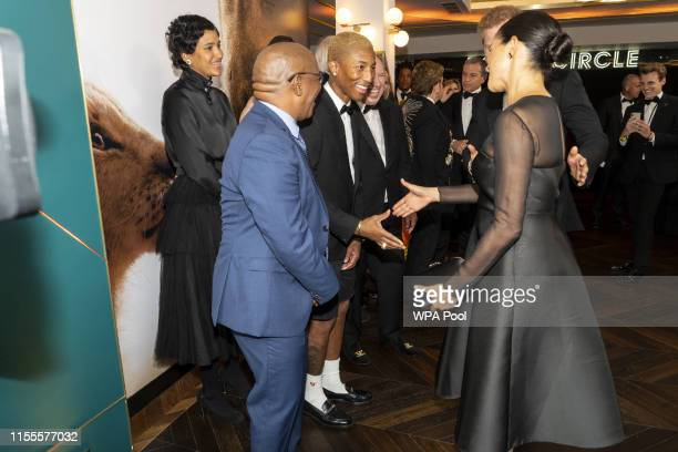 """Prince Harry, Duke of Sussex and Meghan, Duchess of Sussex greet US singer Pharrell Williams at the European Premiere of Disney's """"The Lion King"""" at..."""