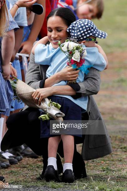 Prince Harry Duke of Sussex and Meghan Duchess of Sussex interact with Luke Vincent 5 after arriving at Dubbo Airport on October 17 2018 in Dubbo...