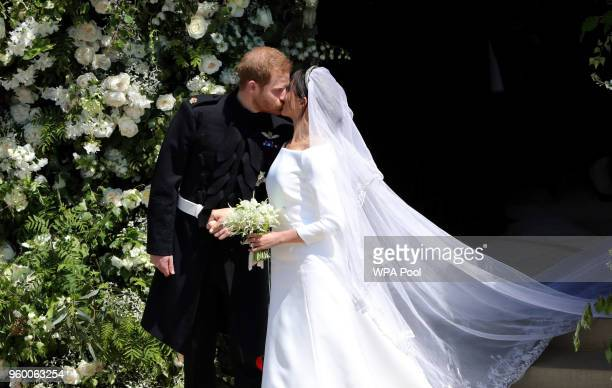 Prince Harry Duke of Sussex and Meghan Duchess of Sussex kiss as they leave St George's Chapel Windsor Castle after their wedding ceremony on May 19...