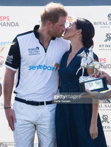 Prince Harry Duke of Sussex and Meghan Duchess of Sussex kiss at the trophy presentation at the Sentebale Polo 2018 held at the Royal County of...