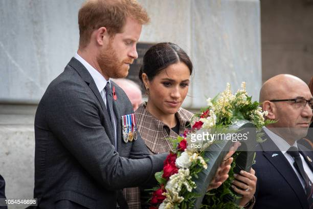 Prince Harry, Duke of Sussex and Meghan, Duchess of Sussex lay ferns and a wreath at the tomb of the Unknown Warrior while they visit the newly...