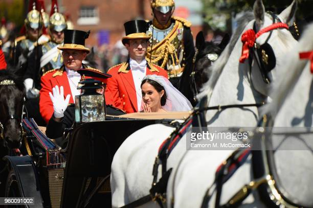 Prince Harry Duke of Sussex and Meghan Duchess of Sussex leave Windsor Castle in the Ascot Landau carriage during a procession after getting married...