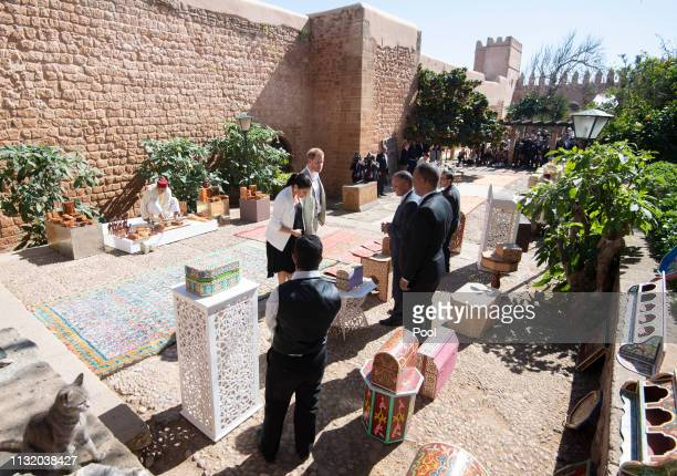 Prince Harry Duke of Sussex and Meghan Duchess of Sussex look at items from a merchant in the walled public Andalusian Gardens during a visit on...