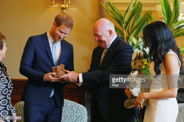 Prince Harry Duke of Sussex and Meghan Duchess of Sussex look at bush hats with Australia's Governor General Peter Cosgrove and his wife Lynne...