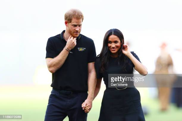 Prince Harry Duke of Sussex and Meghan Duchess of Sussex look on during the pregame ceremonies before the MLB London Series game between Boston Red...