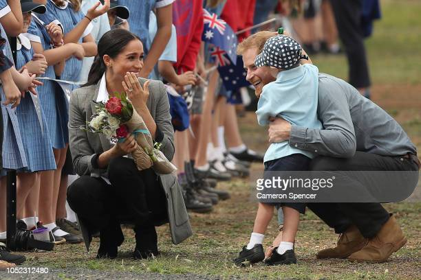 Prince Harry Duke of Sussex and Meghan Duchess of Sussex meet with local children as they arrive at Dubbo Airport on October 17 2018 in Dubbo...