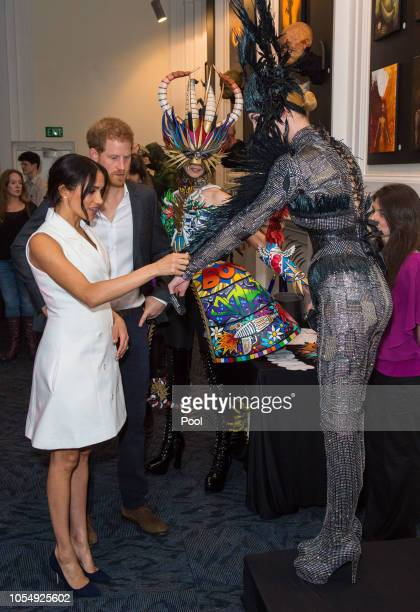 Prince Harry Duke of Sussex and Meghan Duchess of Sussex pose for a photo with models wearing the work of industry leading artists in film sculpture...