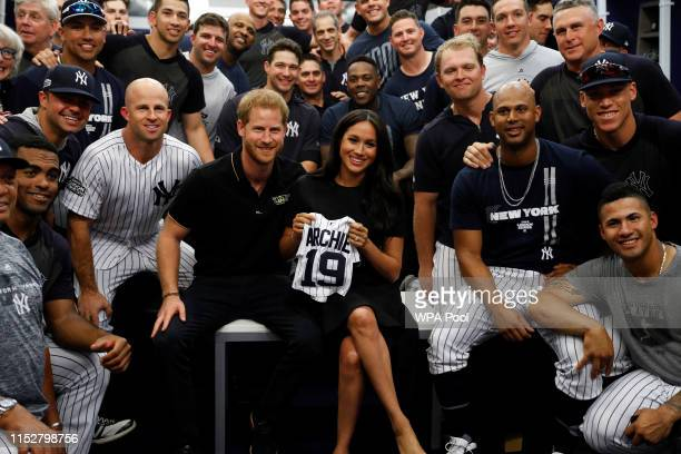 Prince Harry Duke of Sussex and Meghan Duchess of Sussex pose for a photo with the New York Yankees before their game against the Boston Red Sox at...