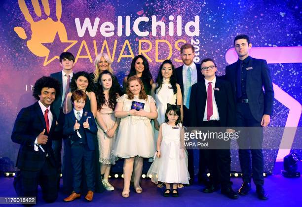 Prince Harry Duke of Sussex and Meghan Duchess of Sussex pose for a group photograph with award winners and presenters during the WellChild Awards at...