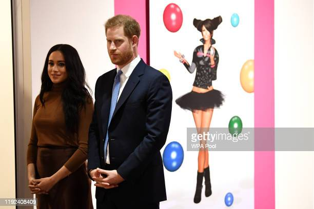 Prince Harry Duke of Sussex and Meghan Duchess of Sussex react as they view a special exhibition of art by Indigenous Canadian artist Skawennati in...