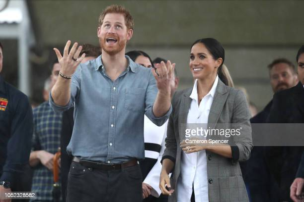 Prince Harry, Duke of Sussex and Meghan, Duchess of Sussex react as they look out towards the heavy rain and storm as they visit the Clontarf...