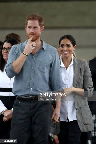 Prince Harry Duke of Sussex and Meghan Duchess of Sussex react as they look out towards the heavy rain and storm as they visit the Clontarf...