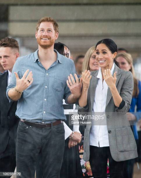 Prince Harry Duke of Sussex and Meghan Duchess of Sussex react to the heavy rain as they visit students from Dubbo College Senior Campus on October...