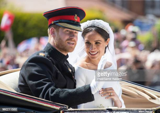 Prince Harry Duke of Sussex and Meghan Duchess of Sussex ride by carriage following their wedding at St George's Chapel Windsor Castle on May 19 2018...