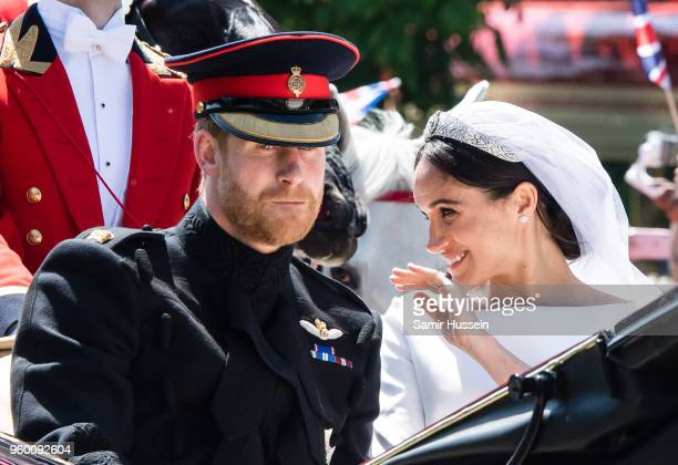 Prince Harry Duke of Sussex and Meghan Duchess of Sussex ride in the Ascot Landau carriage during the procession after getting married at St George's...