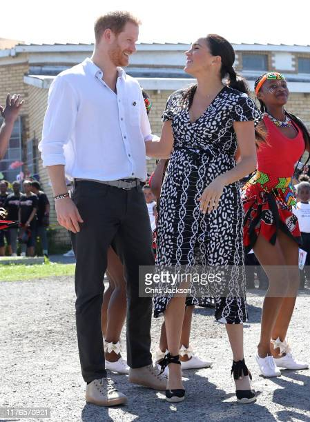 Prince Harry, Duke of Sussex and Meghan, Duchess of Sussex smile as they watch dancers during their visit to a Justice Desk initiative in Nyanga...