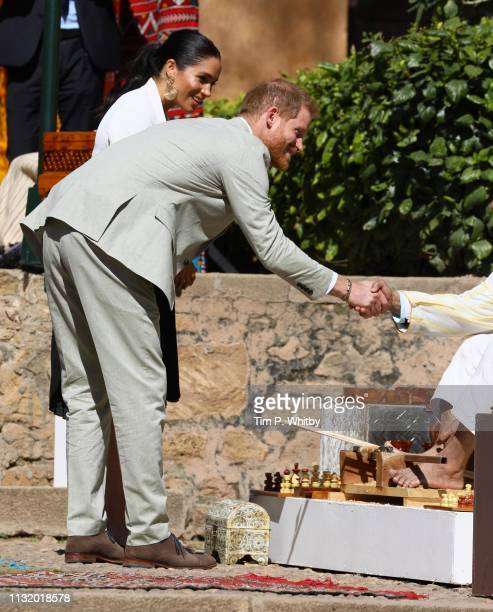Prince Harry Duke of Sussex and Meghan Duchess of Sussex speak to a merchant in the walled public Andalusian Gardens during a visit on February 25...