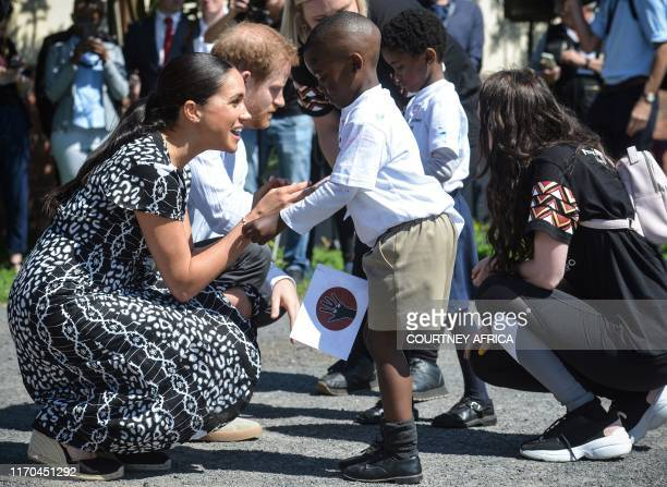 Prince Harry Duke of Sussex and Meghan Duchess of Sussex speak with children as they arrive to visit the Justice desk an NGO in the township of...